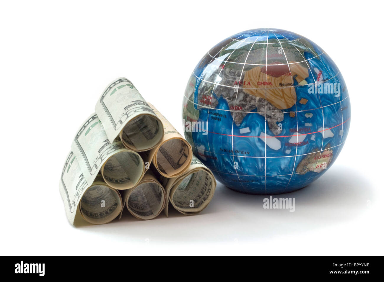 Global economics represented by a pile of rolled dollars stacked beside a small globe - Stock Image