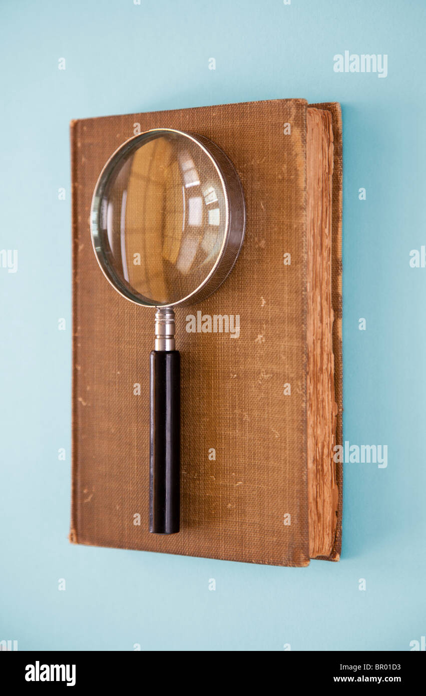 magnifying glass sits on closed book - Stock Image