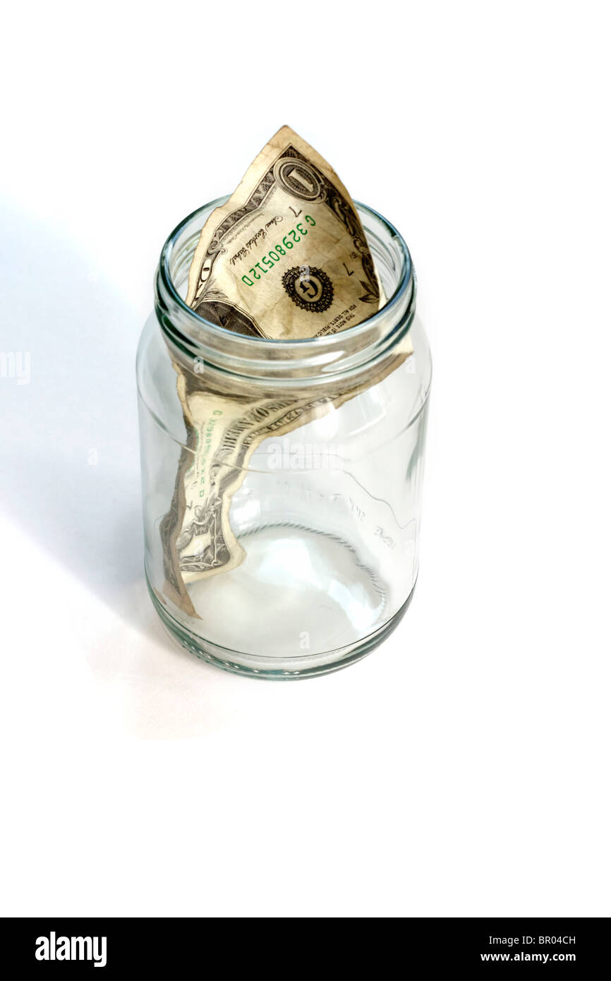 Nearly empty glass jar with a crumpled dollar bill - Stock Image