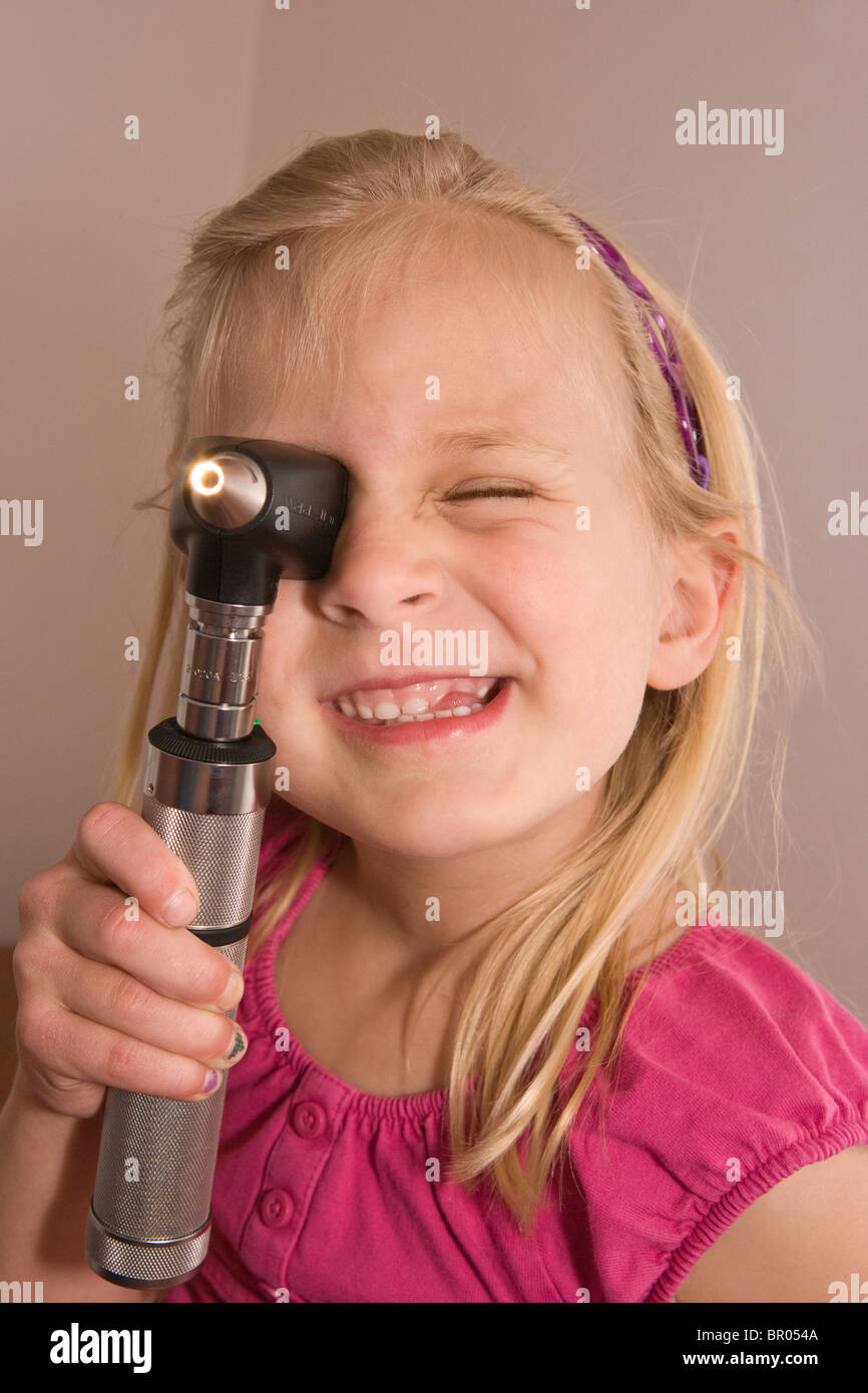 young girl holding an otoscope and learning about the inner ear in a doctor's office - Stock Image