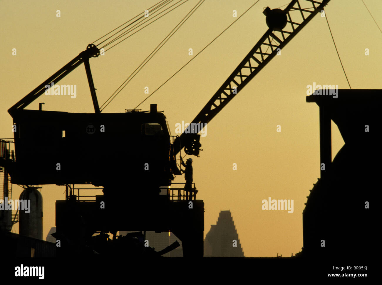 Silhouette of a man near a large crane in a metal scrap yard. - Stock Image