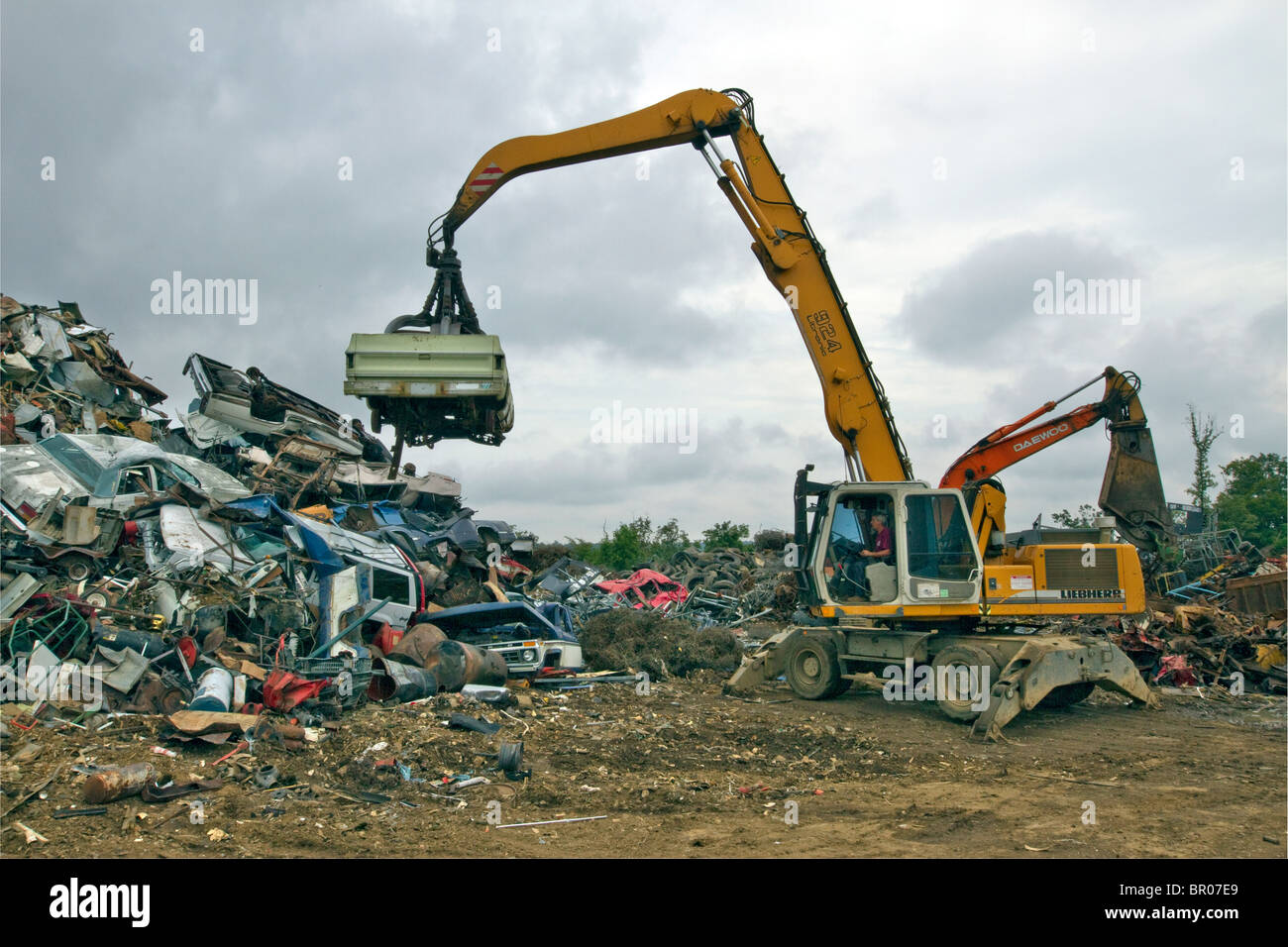 Car being unloaded on a pile in a metal scrap yard. - Stock Image