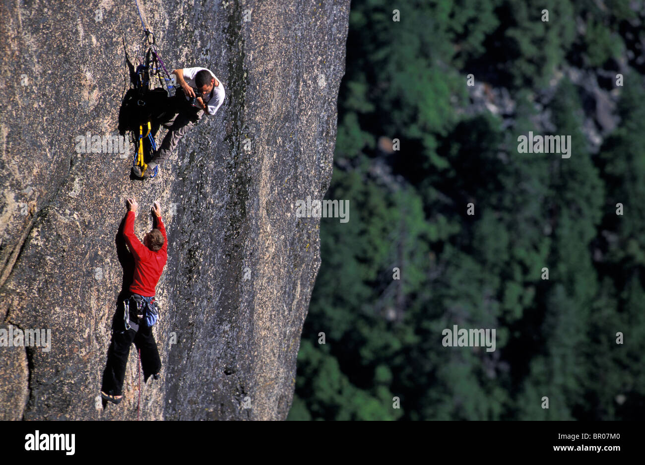 A male photographer taking pictures of a male rock climber lead climbing on a granite big wall route. - Stock Image