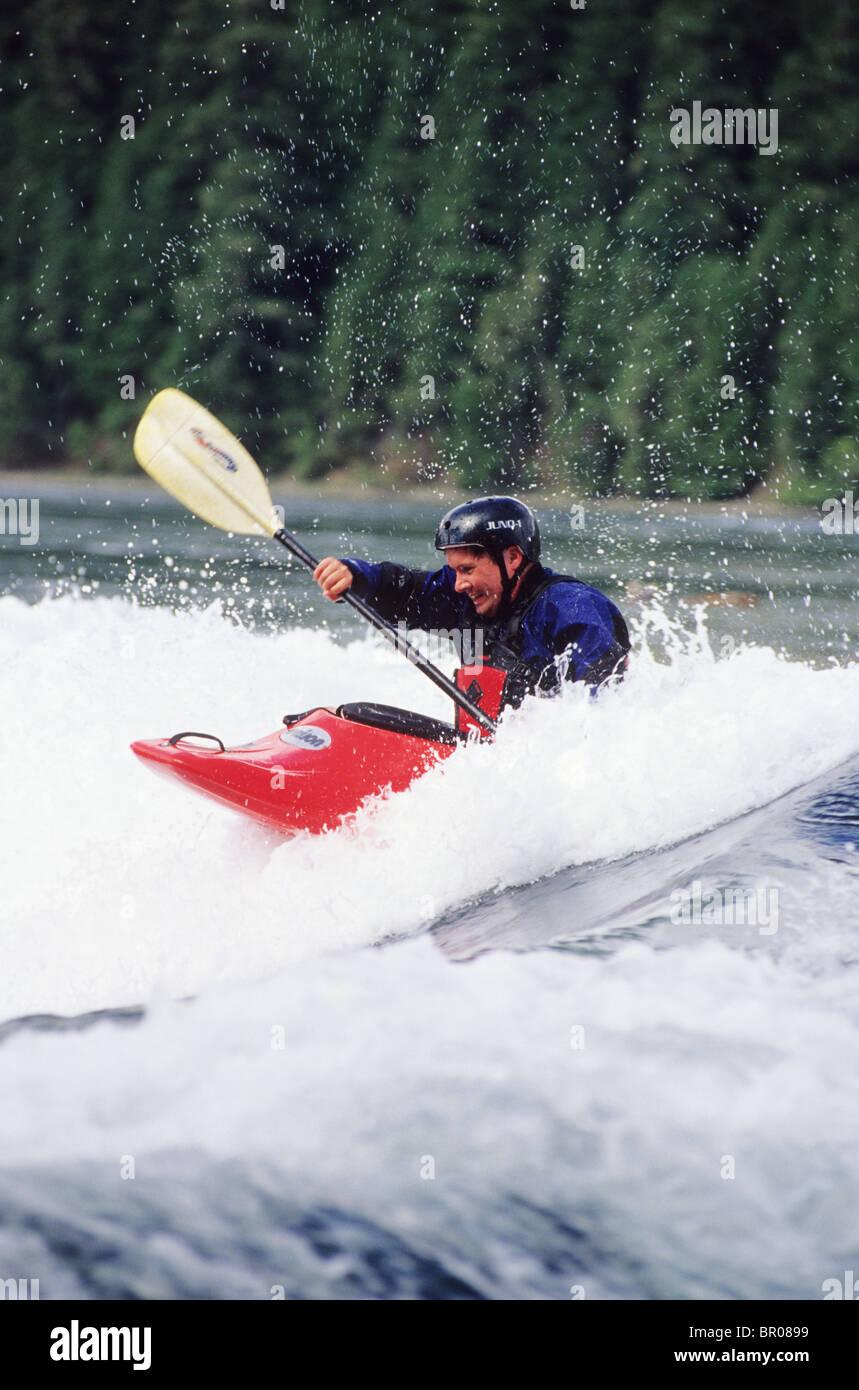 A man whitewater kayaking. - Stock Image