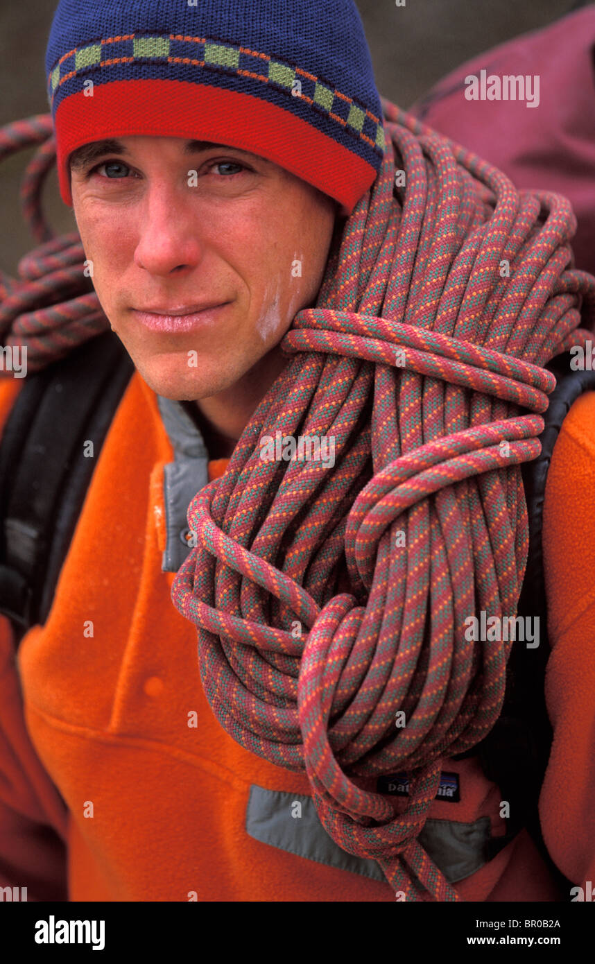 A male rock climber with a rope over his shoulder. - Stock Image