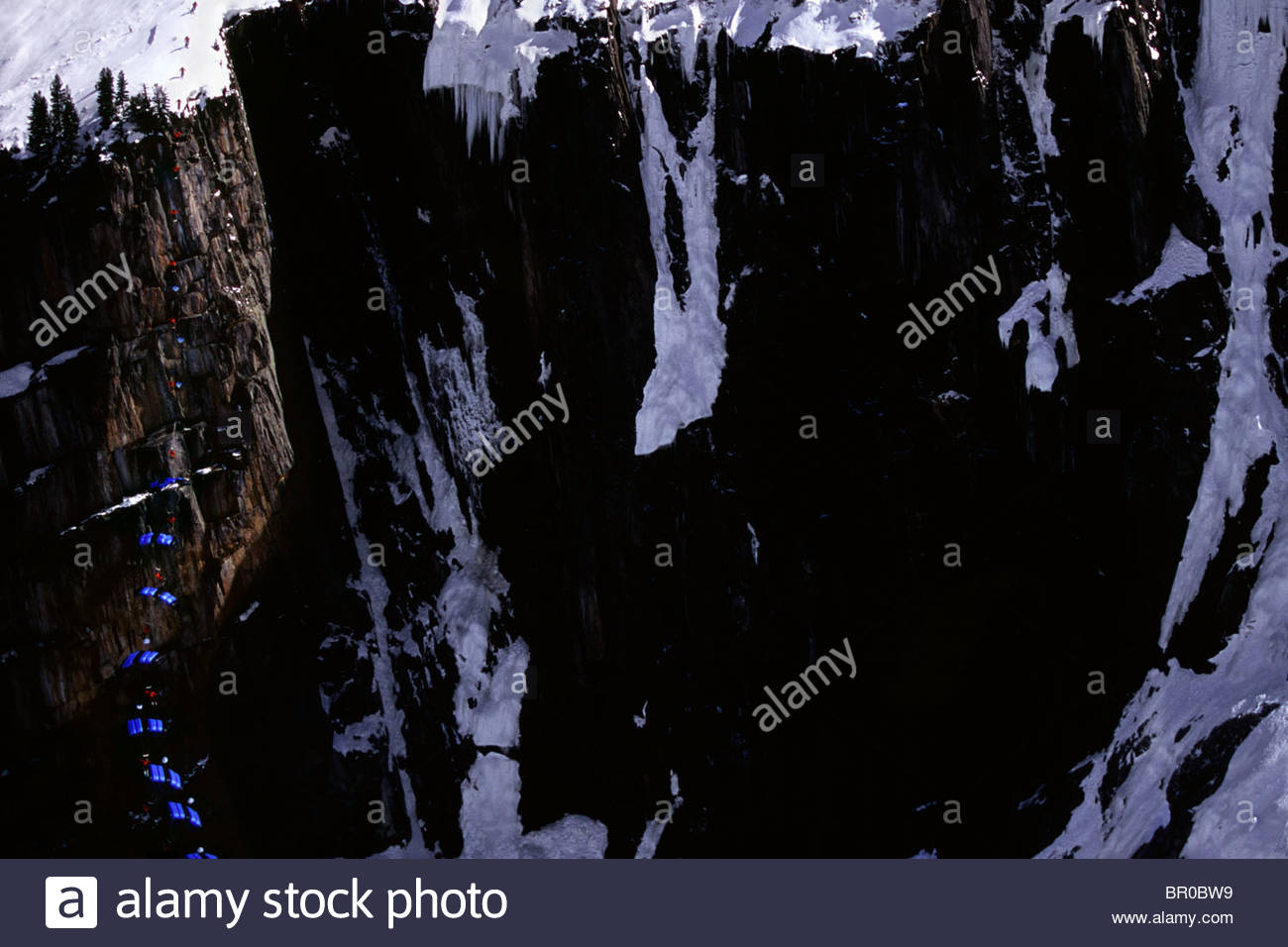 Skier basejumping from a cliff over the argentiere glacier.  Chamonix, France. - Stock Image