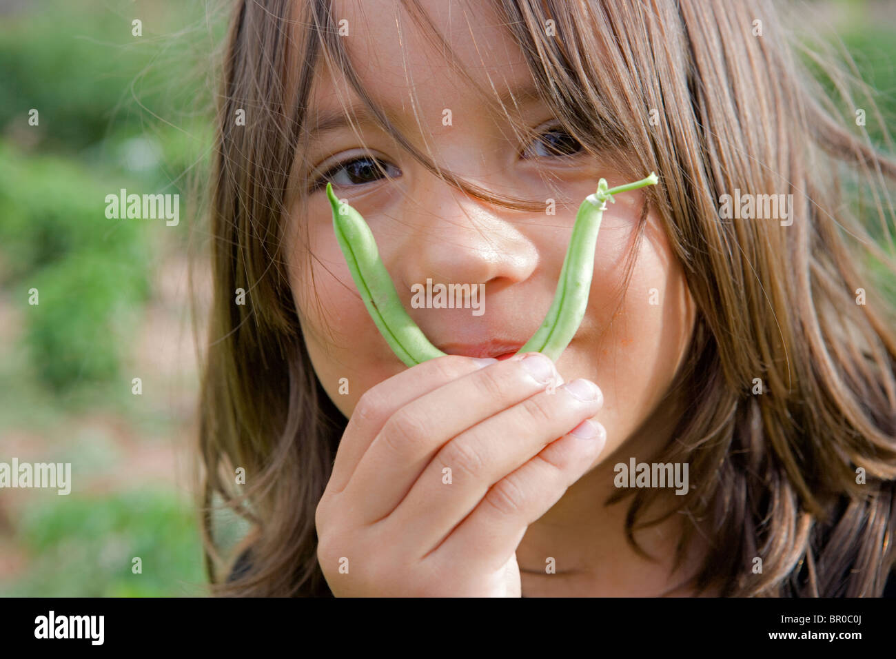 eleven year old picks a green bean and holds it up to his face as a moustache being silly - Stock Image