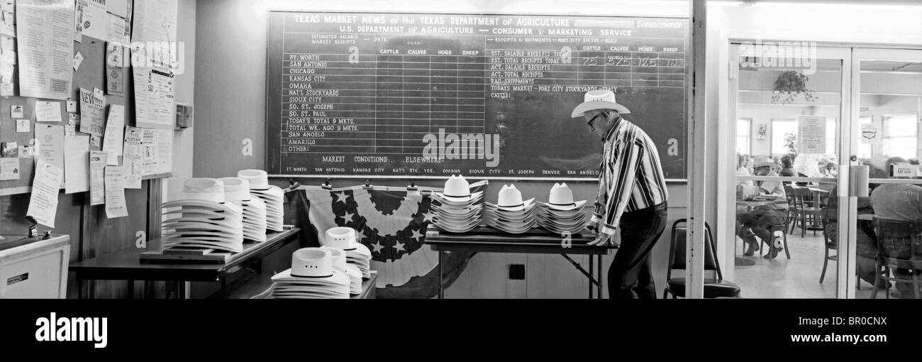 An older cowboy gentleman leans over a table in a building and looks over an assortment of cowboy hats for sale. - Stock Image
