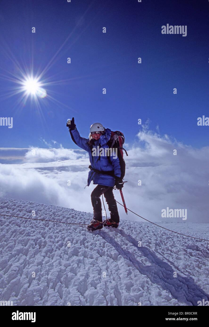 A female mountain climber reaches the summit of Mt. Rainier. Stock Photo