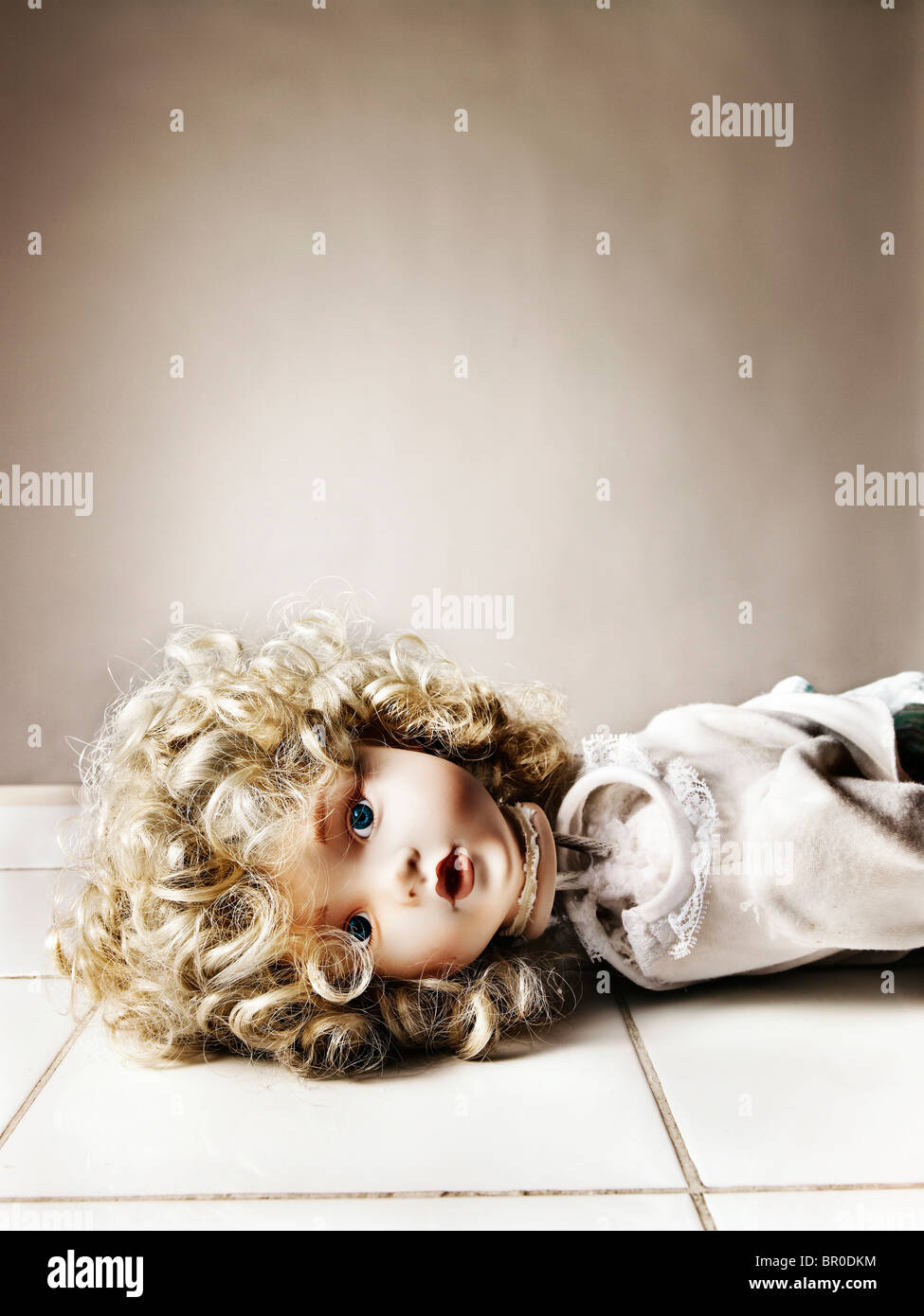 porcelain doll with a broken neck lying on a white tiled floor - Stock Image