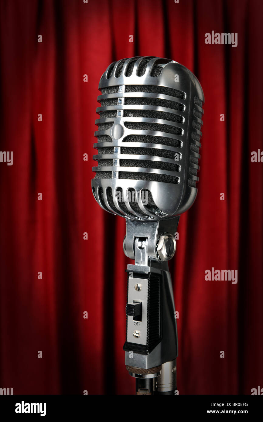 Vintage microphone with red curtain in background - Stock Image