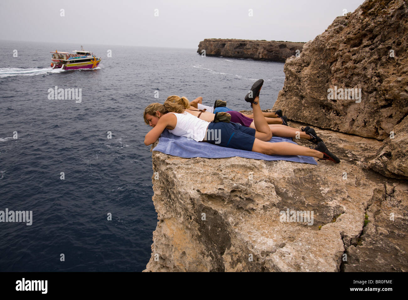 Three women hang out and sunbathe on a cliff above a rock climbing area while waiting for their turns to climb. - Stock Image