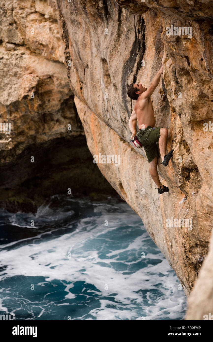 A man deep water soloing / rock climbing. - Stock Image