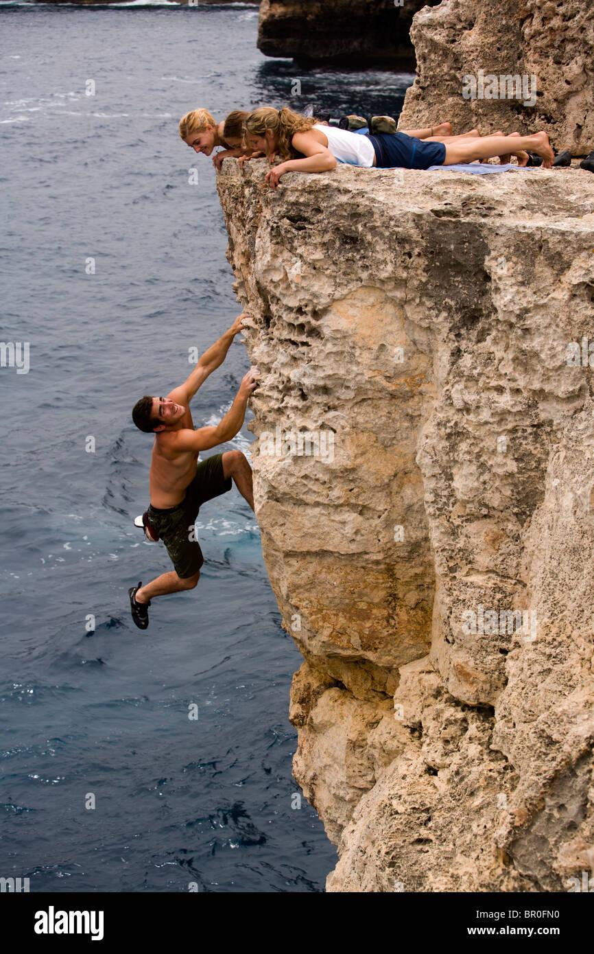 Three women watch a man deep water soloing / rock climbing on a cliff. - Stock Image