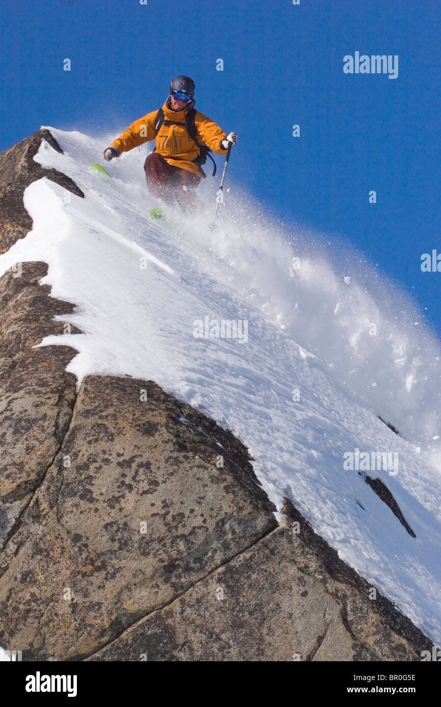 A man skiing powder snow on a rock on Donner Summit in California. - Stock Image