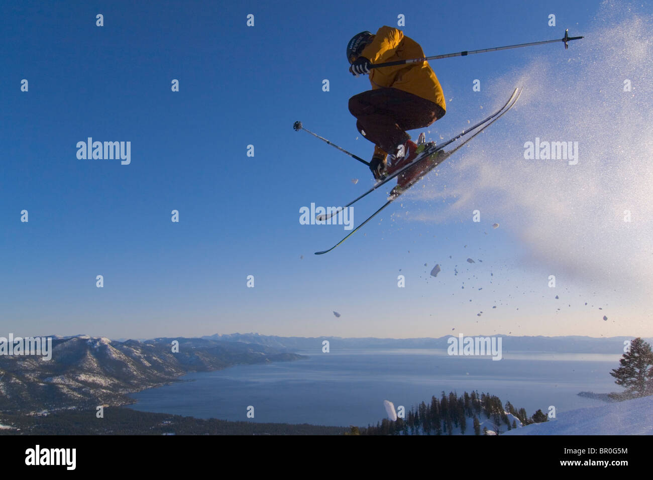 A man jumping on skis above Lake Tahoe in California. - Stock Image