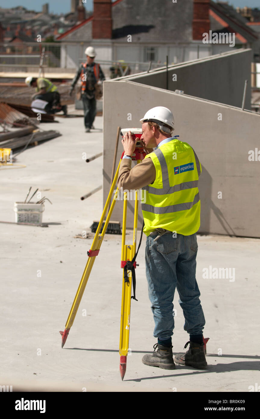 A man, wearing hi vis jacket and full PPE equipment,  working on a building site surveying the location with a Leica - Stock Image