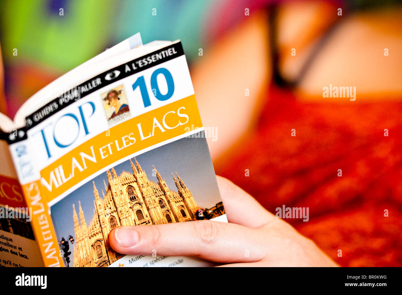 """Woman reading the """"Milan Top 10"""" tourist guide book in french, Milan, Lombardy, Italy. Stock Photo"""