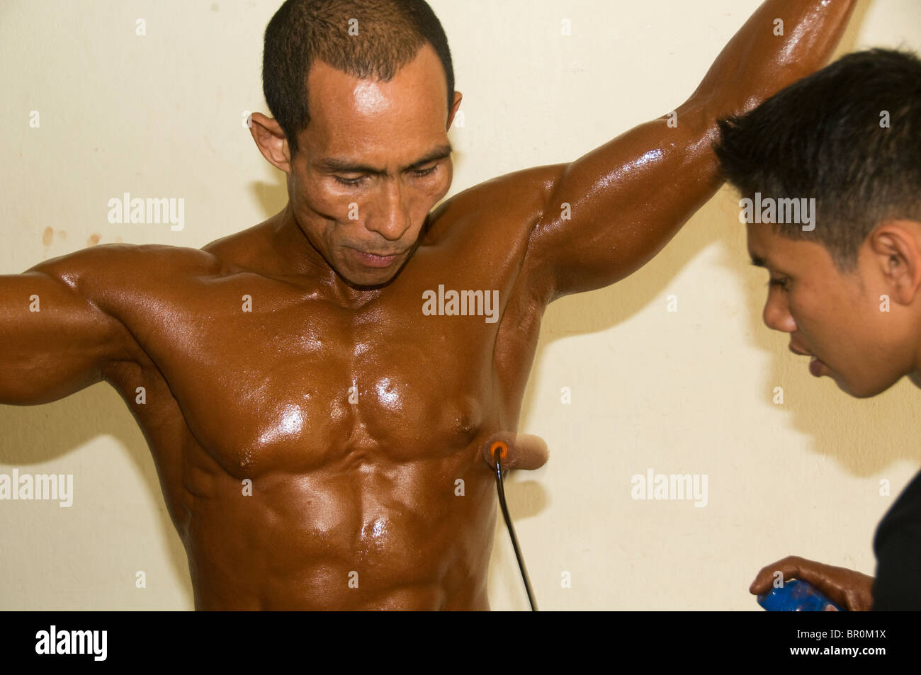 bodybuilder being painted tan before going onstage at a competition in Bangkok Thailand - Stock Image