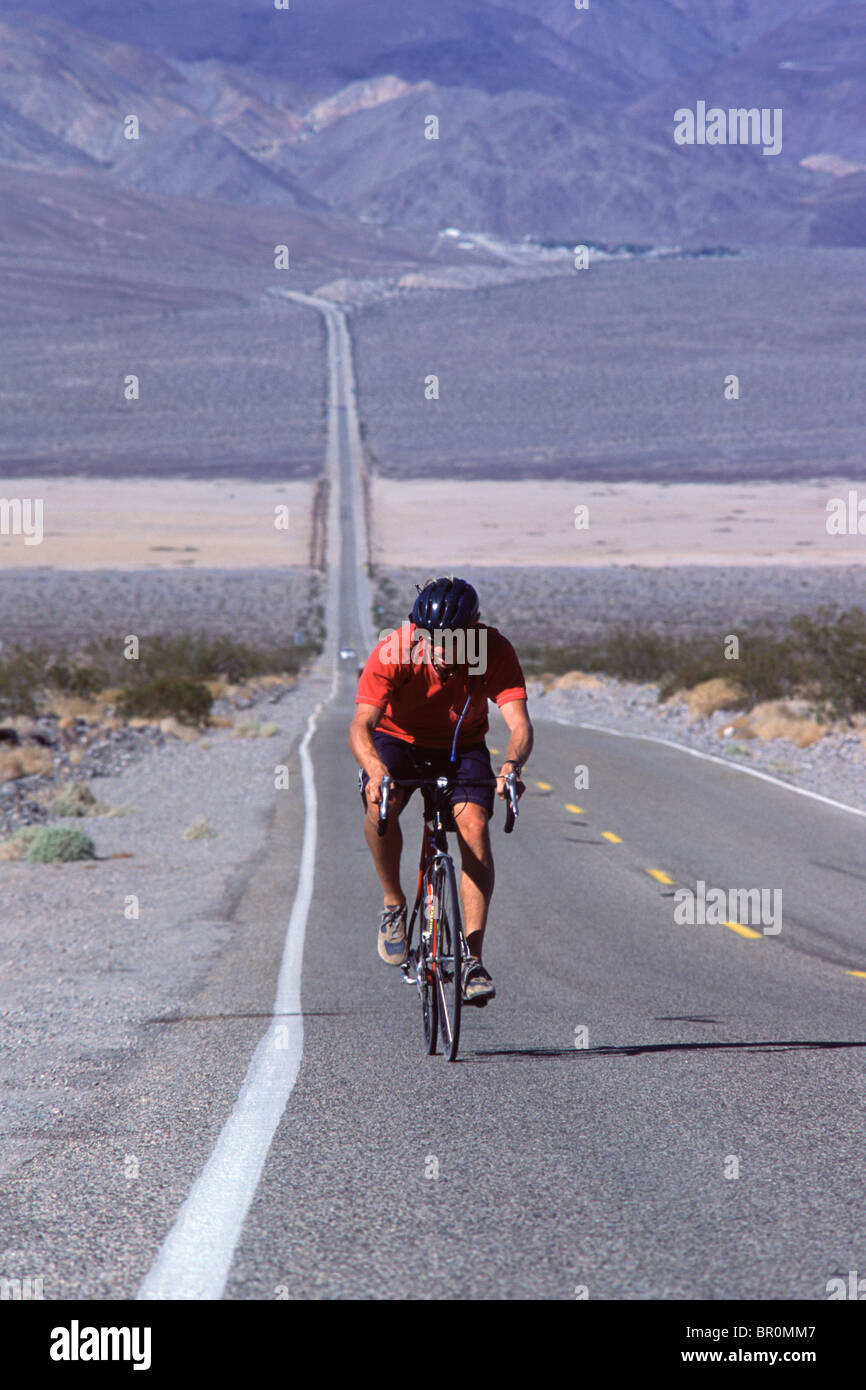 A man biking uphill in the desert on a long road in Death Valley in California. - Stock Image