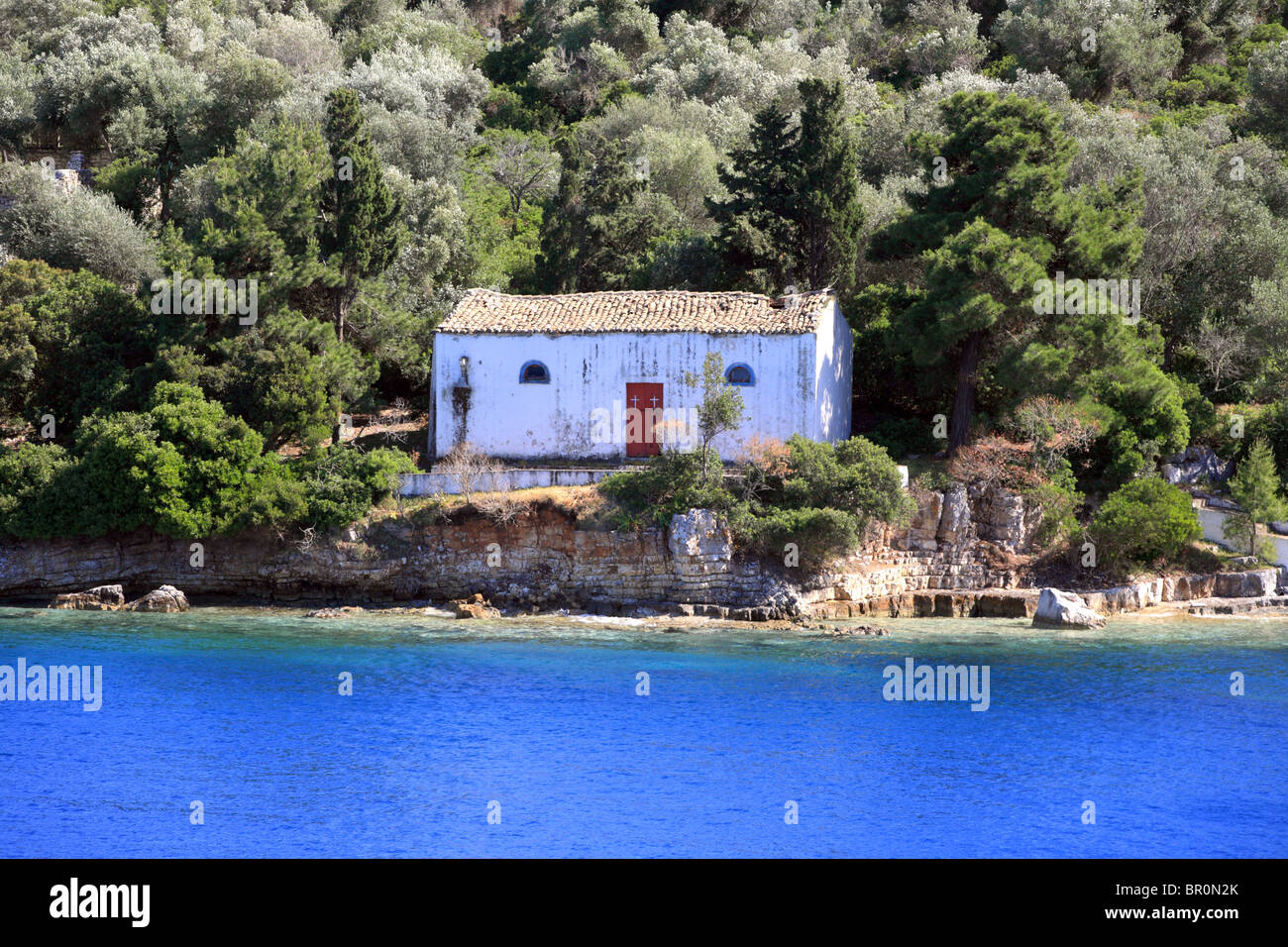 Small Greek chapel at the entrance of Gaios harbour on a small uninhabited island. Paxos. - Stock Image