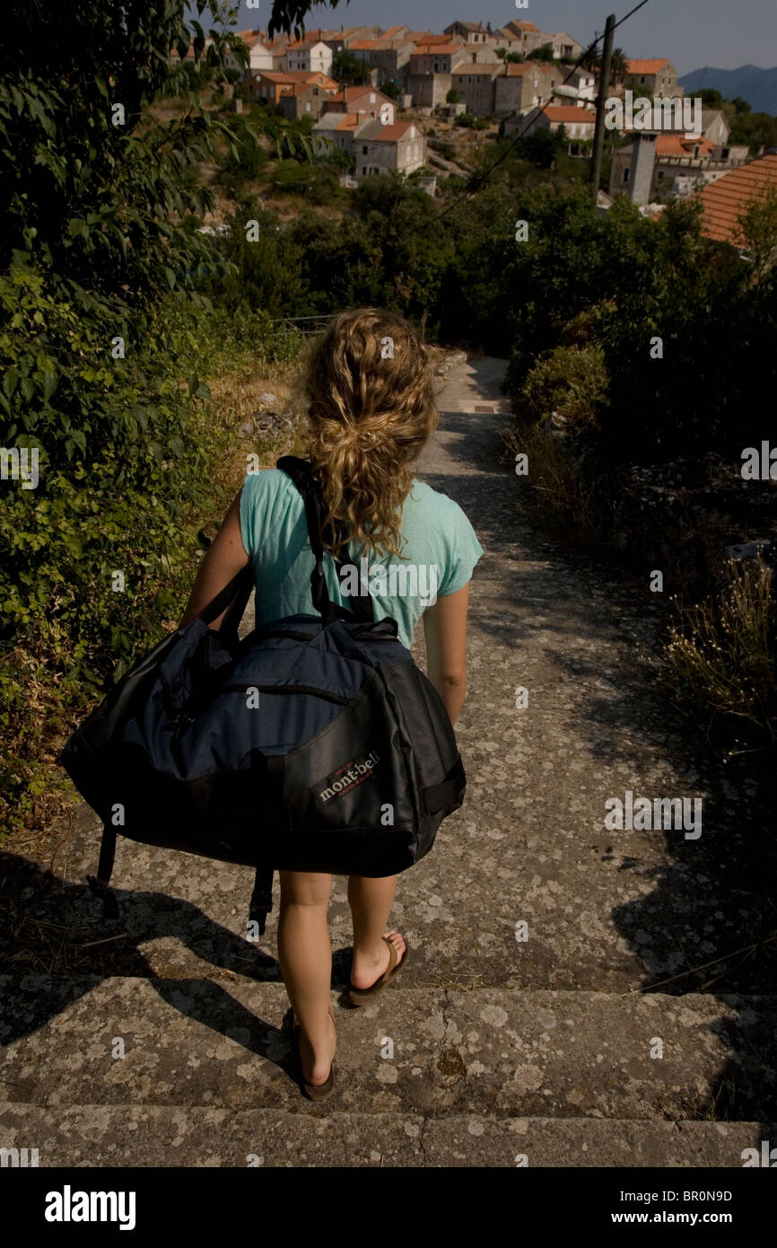 0a701a29 Girl carrying a duffle bag on the remote Island of Iz in Croatia ...