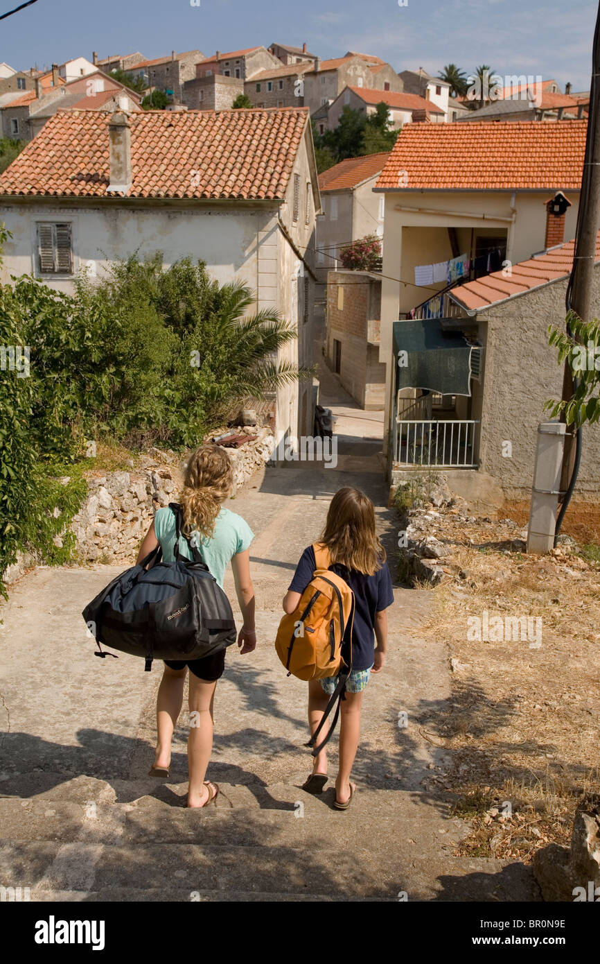 84231966 Two girls carrying duffle bags on the remote Island of Iz in Croatia ...