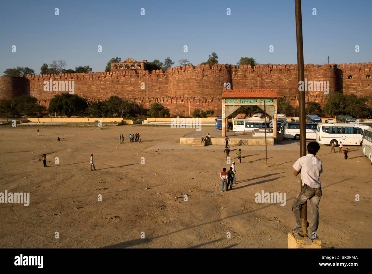 Young local boys playing cricket in a field opposite Agra Fort, Uttar Pradesh, India. - Stock Image