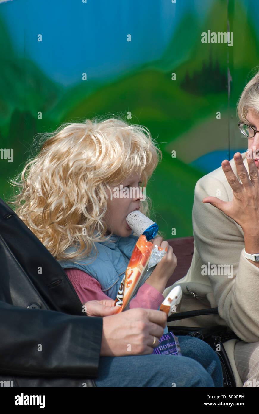 Little blondy girl eating the ice-cream - Stock Image