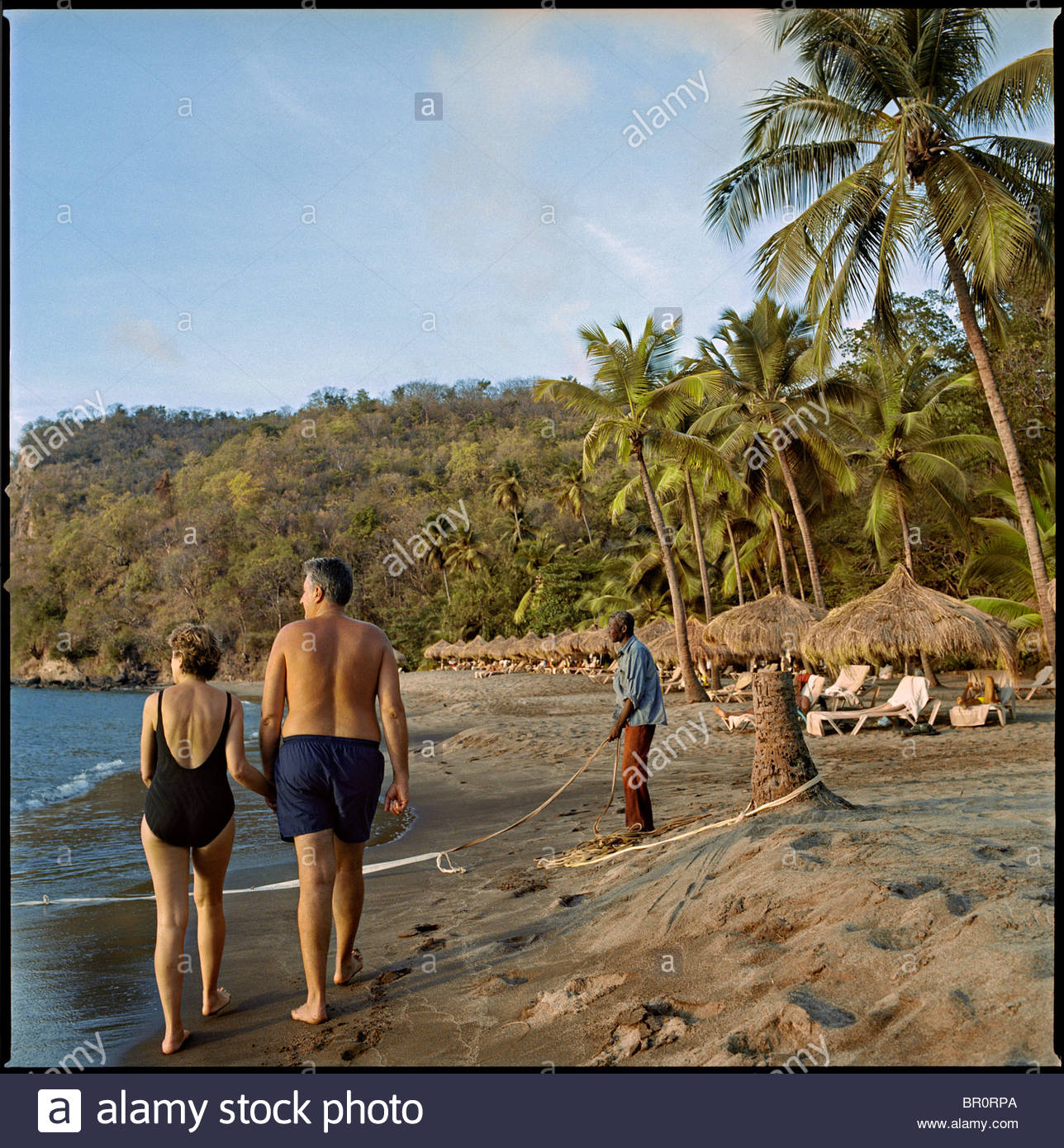 An middle-aged tourist couple strolls along the beach at a resort on St. Lucia Stock Photo