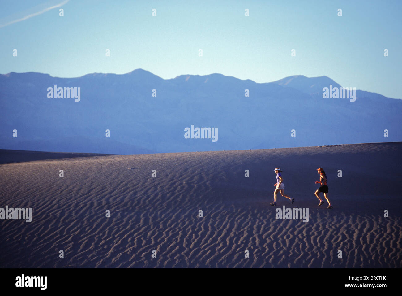 Two women running on a sand dune in Death Valley, California. - Stock Image