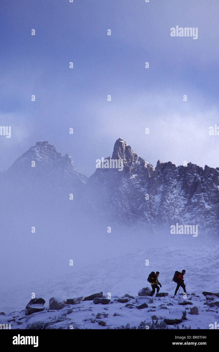 Two people hiking in winter in the Sierra mountains of California. - Stock Image