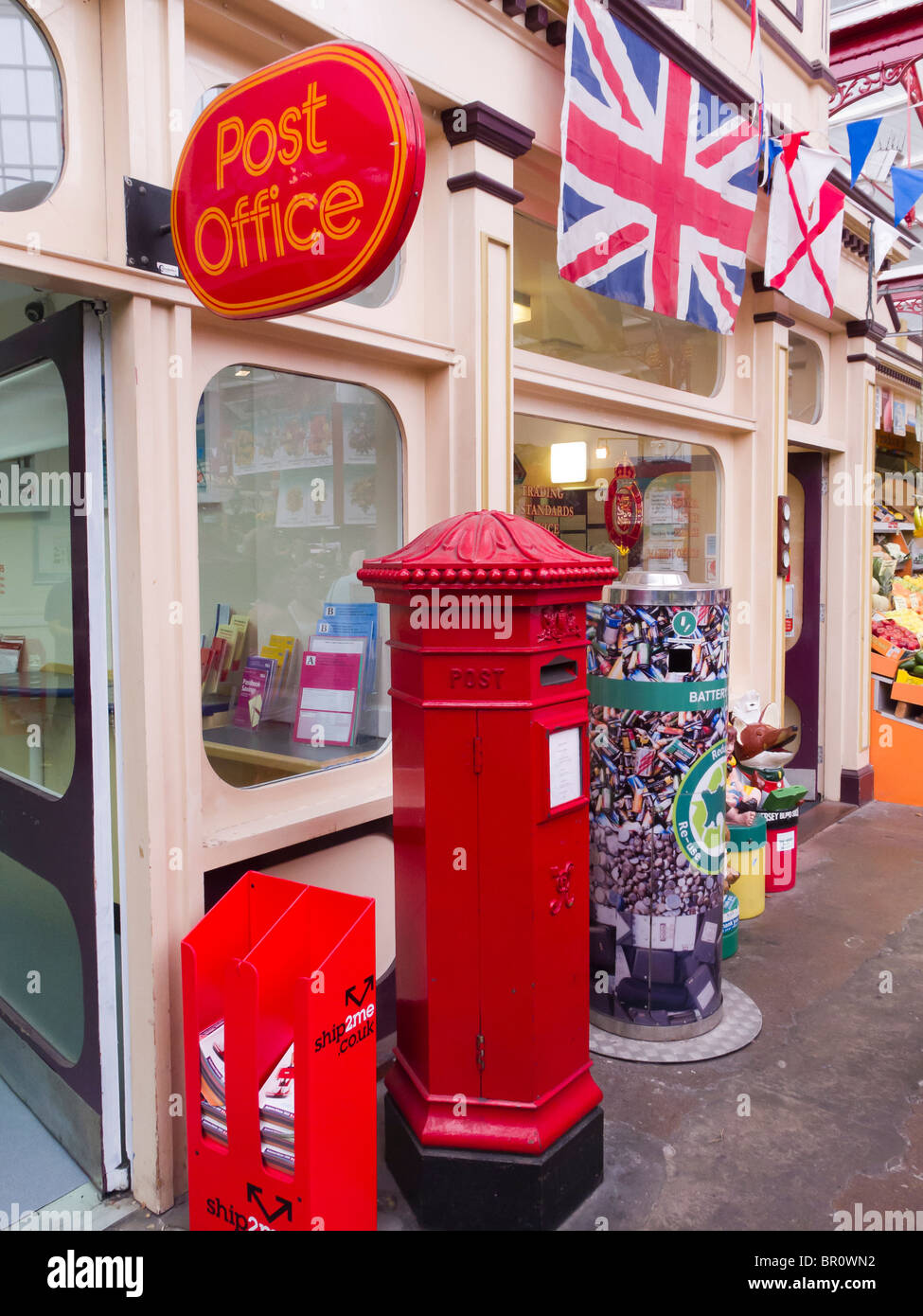 A hexagonal Victorian post box still in use at the Post Office in the covered market in St. Helier, Jersey. - Stock Image