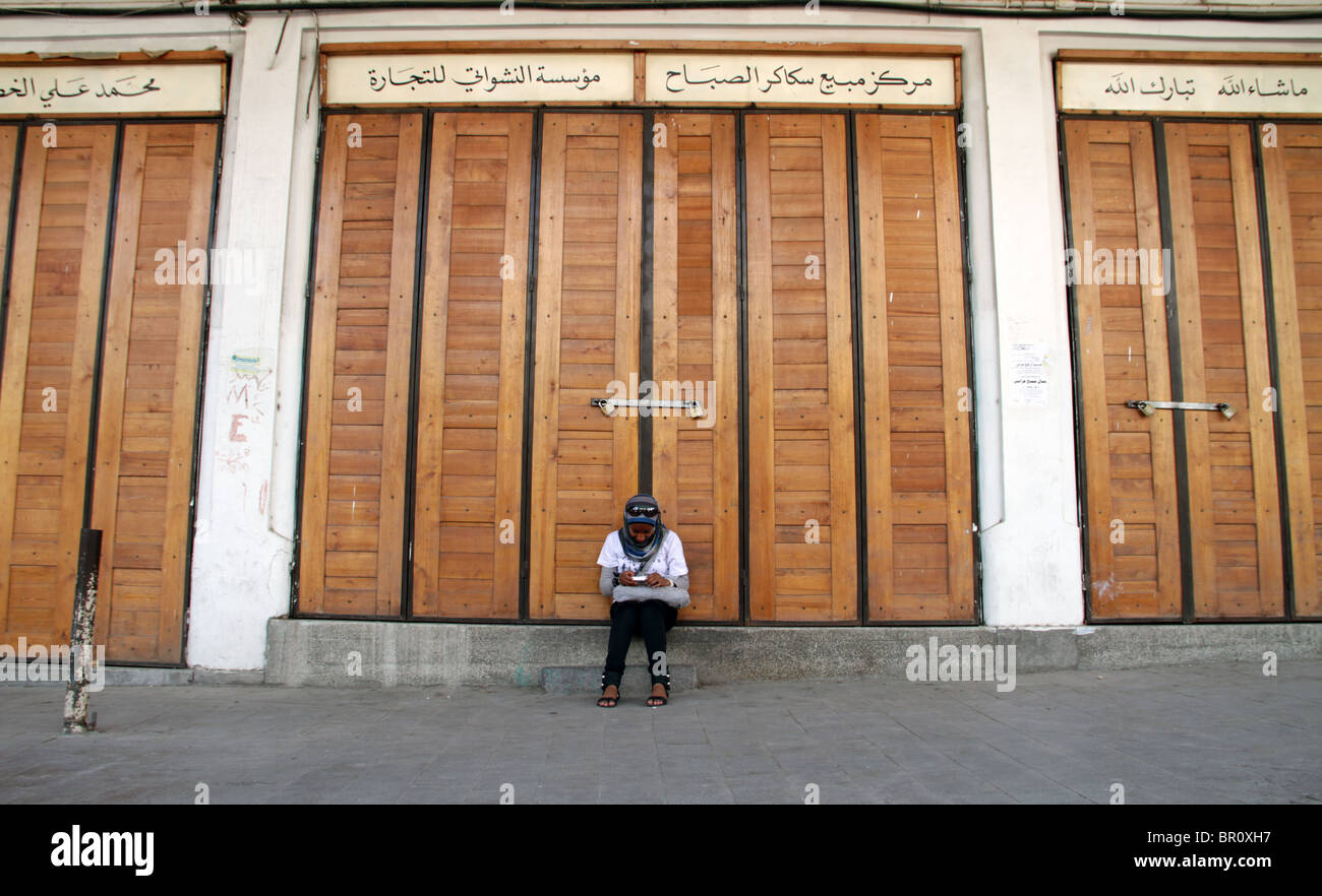 A Palestinian girl sits outside the closed shops viewing images on her Camera during a Refocus training trip in - Stock Image