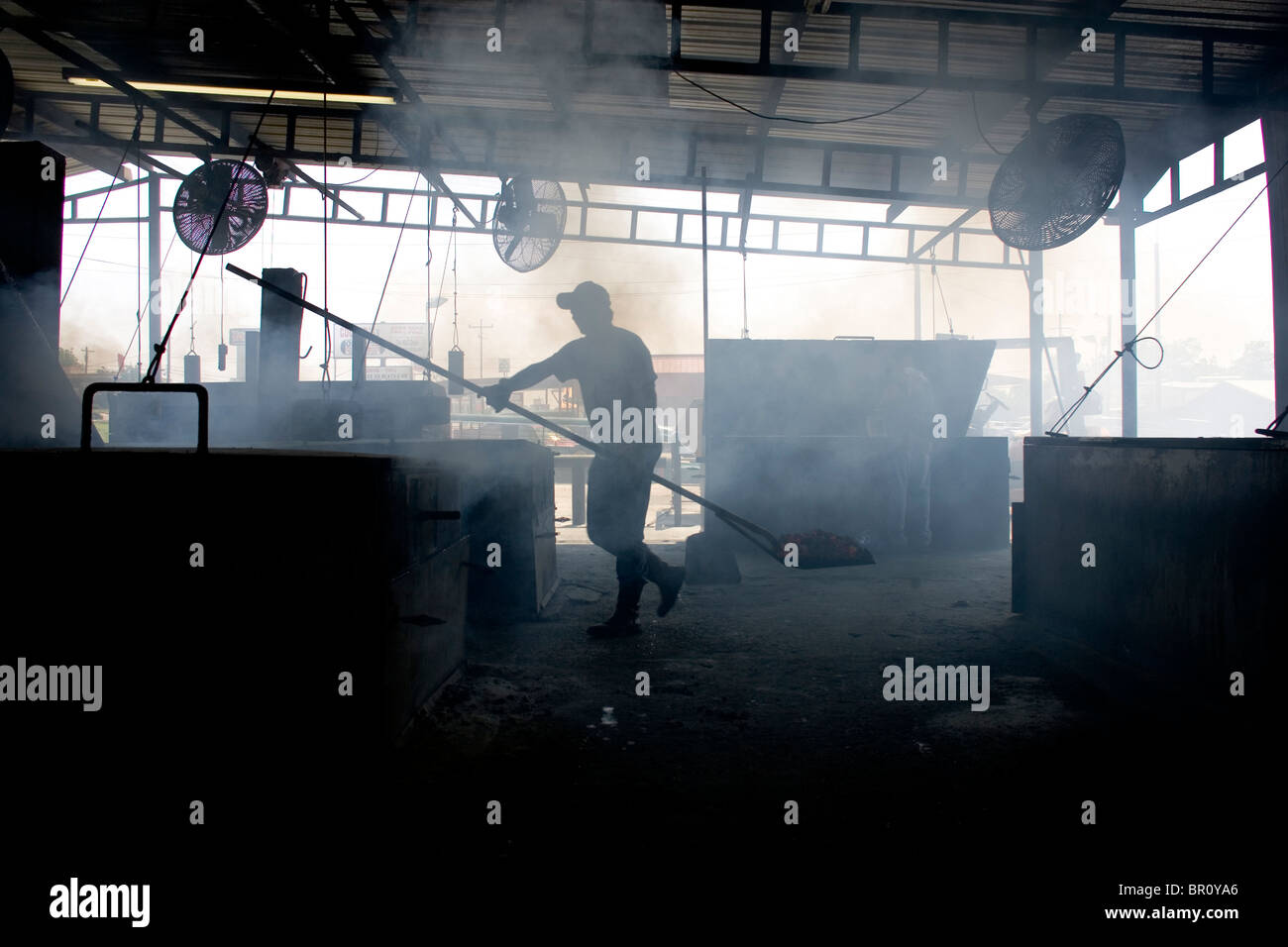 A man is silhouette as he stokes the fires at a barbeque restaurant in Llano, Texas. - Stock Image