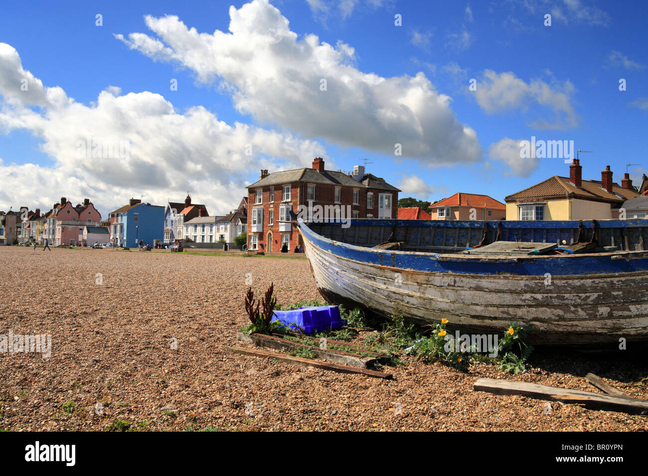 Fishing boat on Aldeburgh beach in front of the row of colourful town houses. Summers day in Suffolk East Anglia. - Stock Image