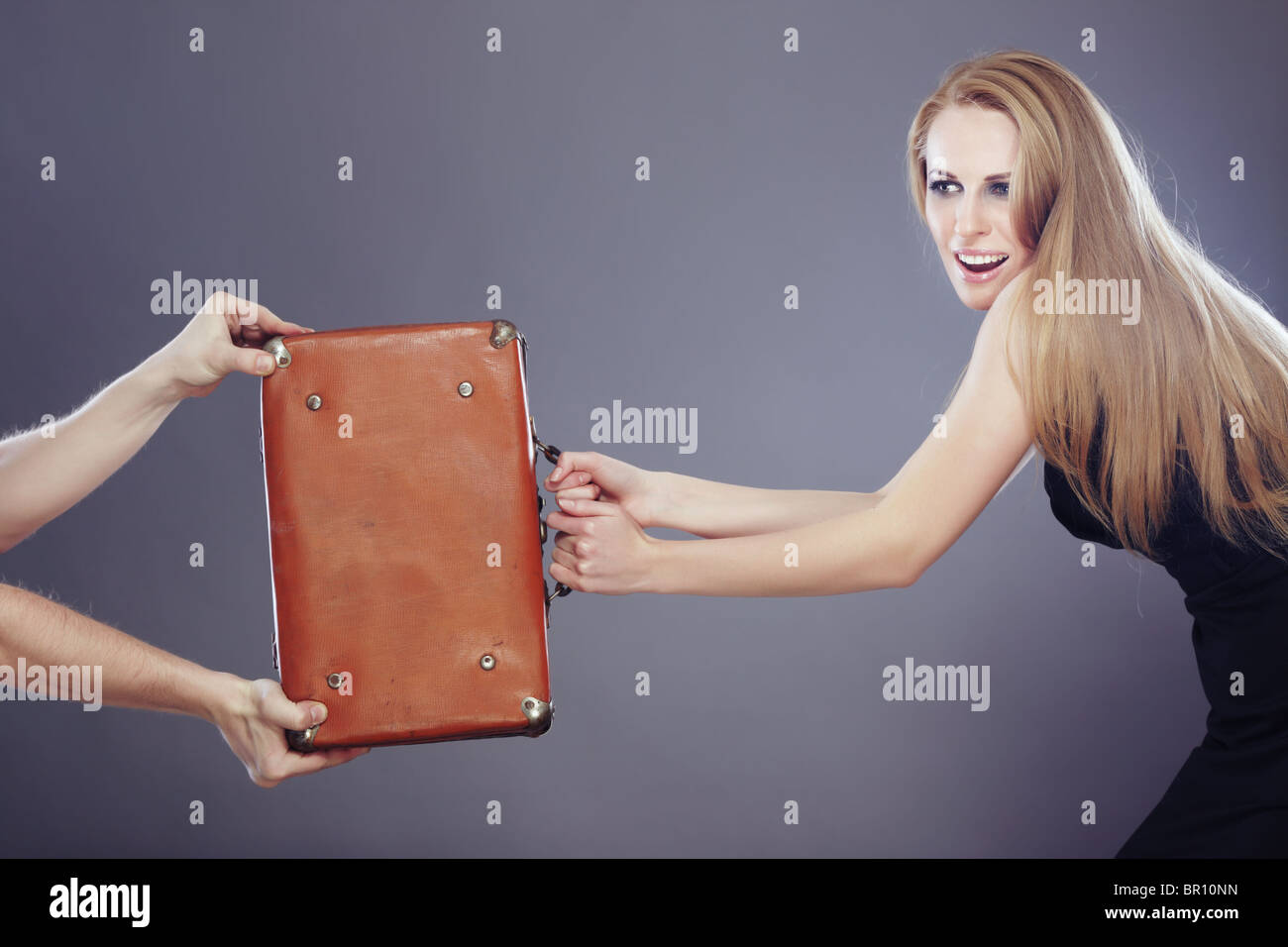 Businesswoman holding bag with money and competitive with hands of somebody - Stock Image