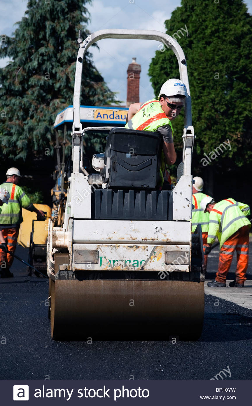 Gang of construction workers laying new tarmac road surface in a Hereford car park, UK. Workman driving a road roller. - Stock Image