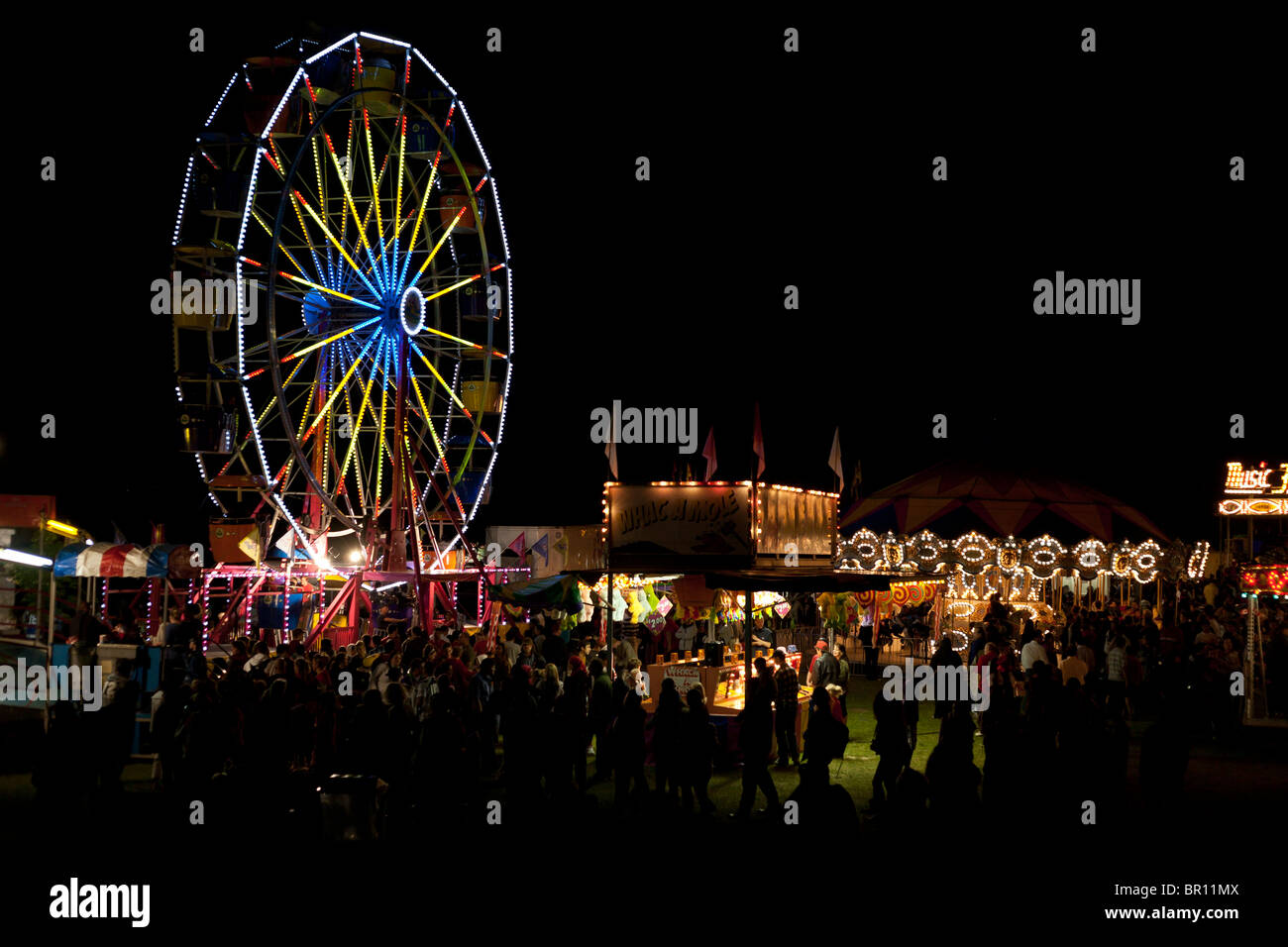 Evening at the Fair. Fairgoers mill about a traveling carnival after dark on Canada Day. A ferris wheel is brightly Stock Photo