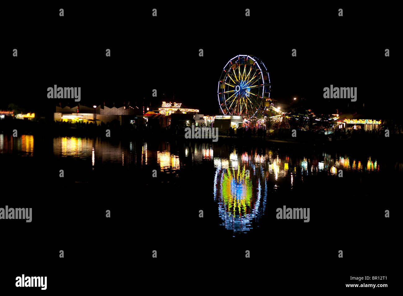 Nighttime Carnival Reflection. Fairgoers mill about a traveling carnival on Canada Day. A ferris wheel is reflected Stock Photo
