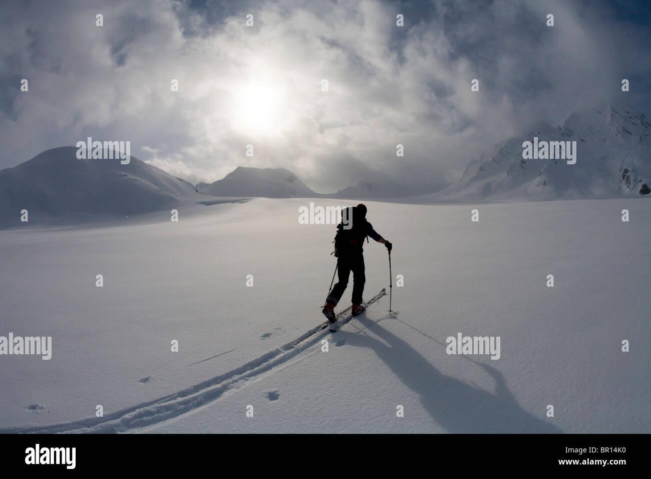 Backcountry skier crosses glacier under late day stormy sky. - Stock Image