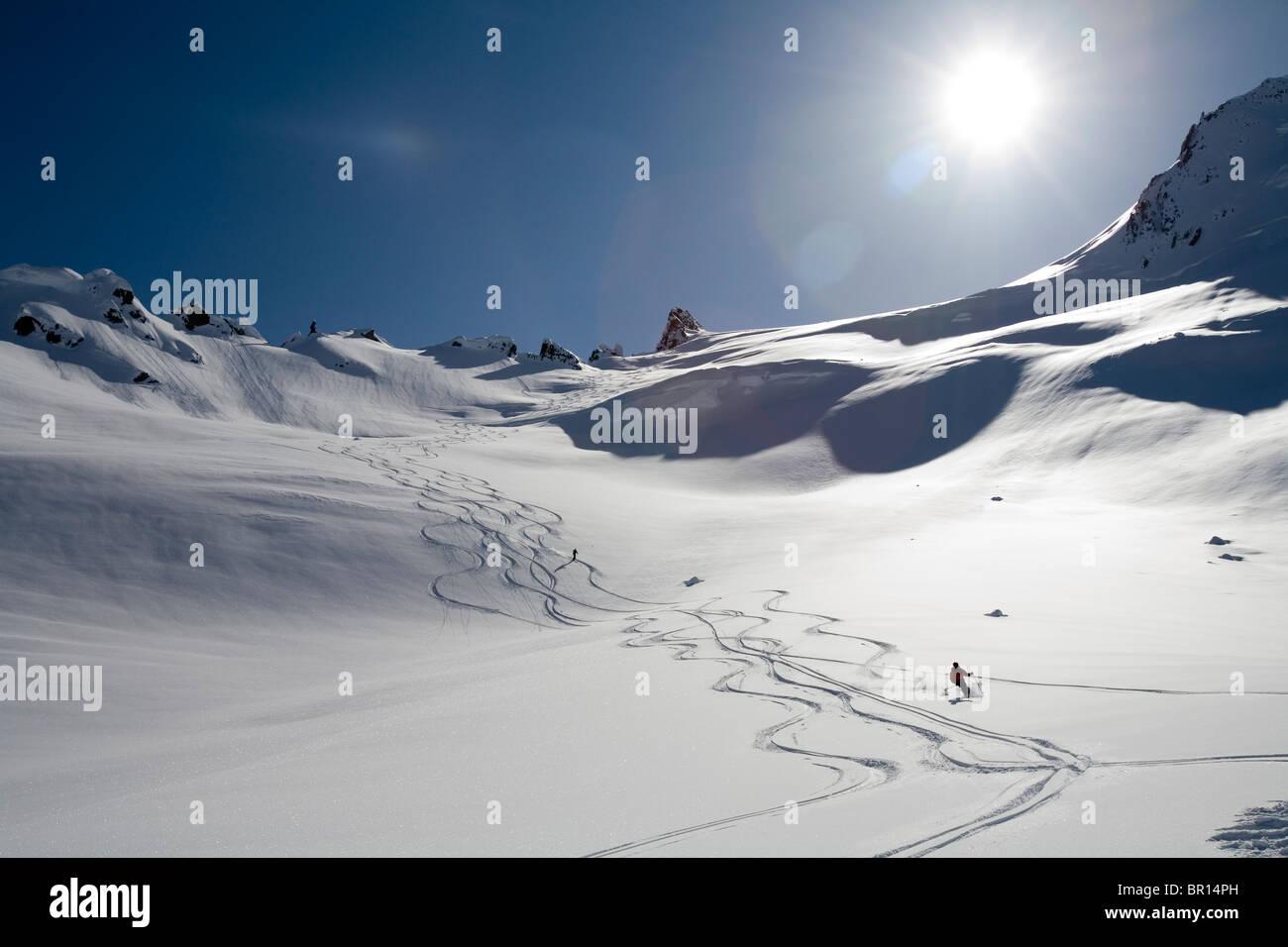 Man skis down hill in Alaska backcountry near Alaska Canada border Stock Photo
