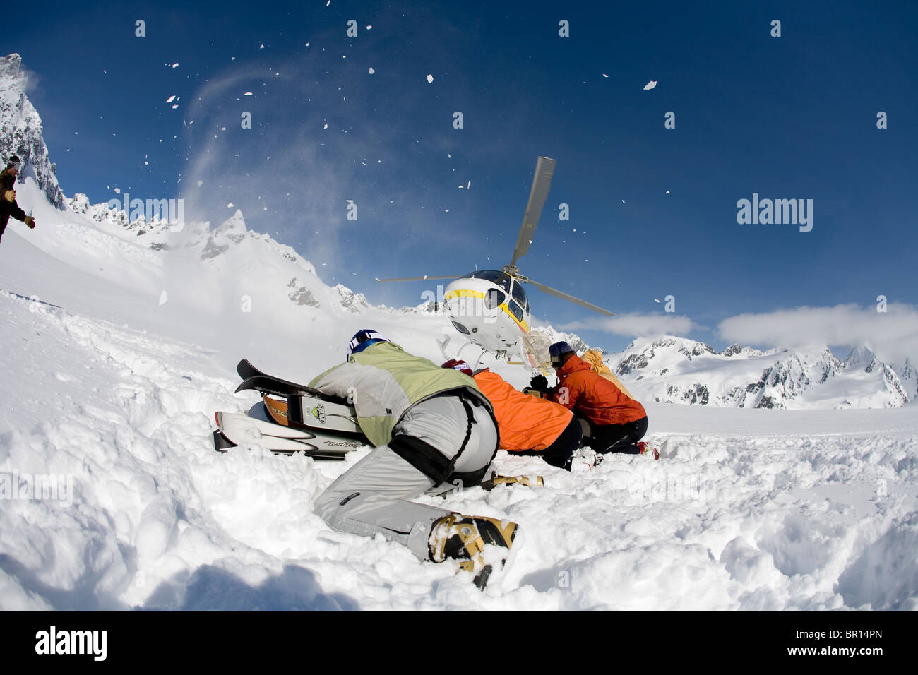 Skiers prepare to load helicopter while skiing in backcountry of southeast Alaska near Haines. - Stock Image