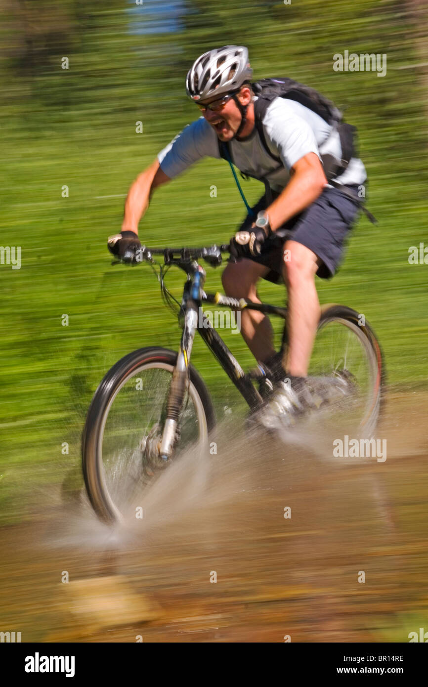 A mountain biker splashing though a stream on Donner Summit in California. (blurred motion) - Stock Image