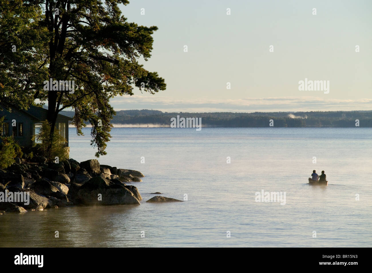 A canoe plies the waters in the morning mist of Sebago Lake in Maine. - Stock Image