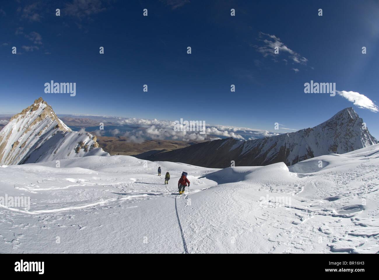 Three climbers on Gurla Mandhata, Tibet. - Stock Image