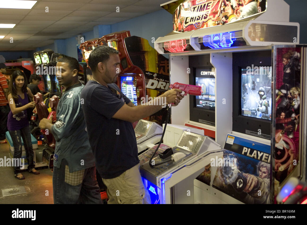 Young men like the video games where they can shoot the bad guys. Video Arcade, Coney Island, Brooklyn, NY. - Stock Image