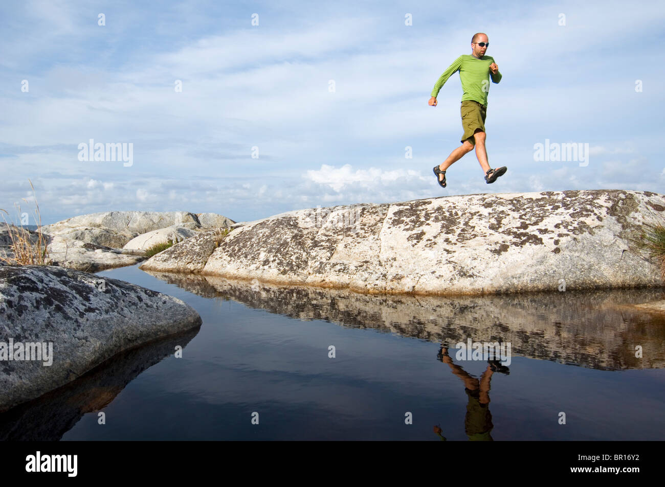 A man running along a rocky ridge above a small pond on one of the hundereds of islands in the archipelago near - Stock Image