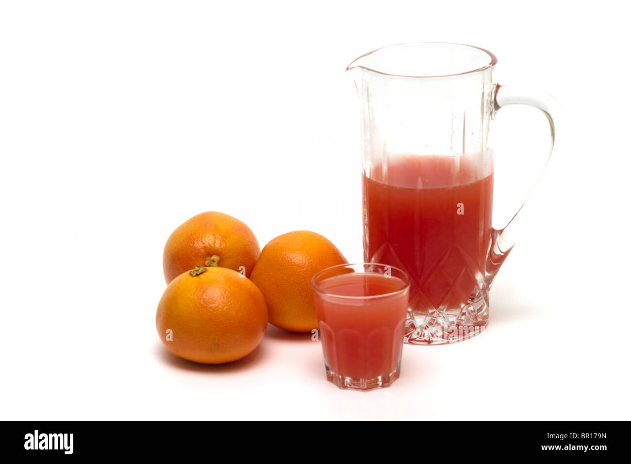 Grapefruits with a pitcher and glass of freshly squeezed grapefruit juice - Stock Image