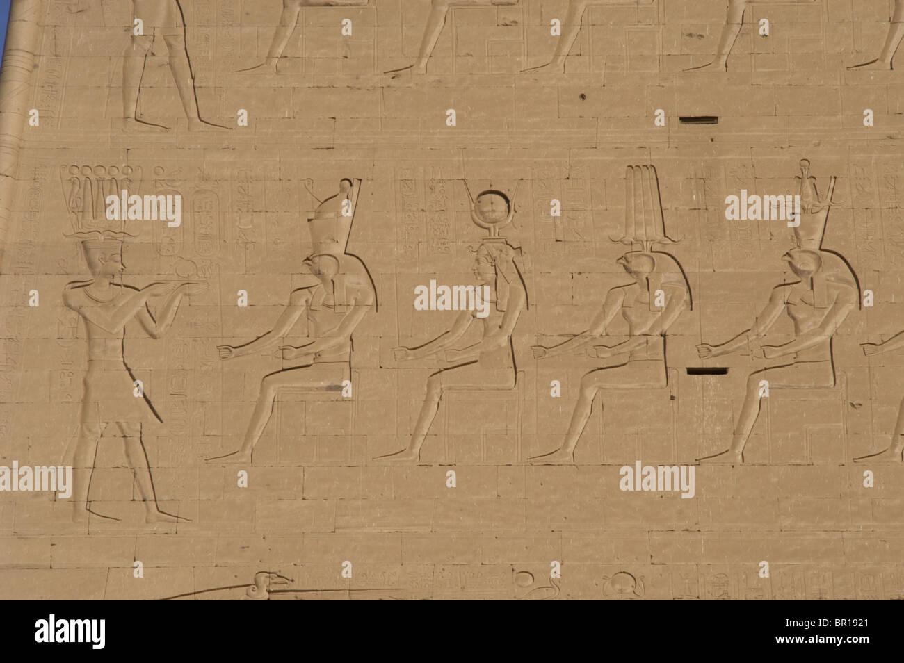 Temple of Horus. Pharaoh before gods. Main entrance. First pylon. Detail. Edfu. Egypt. - Stock Image